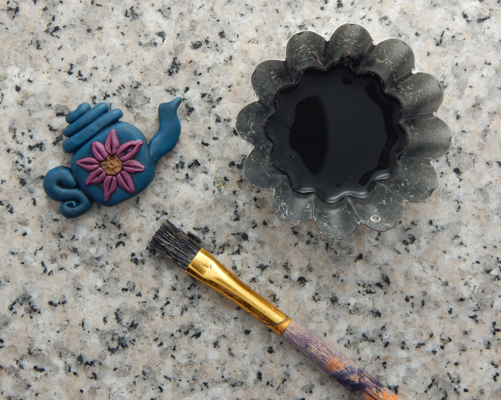 A blue teapot bead with pink flower is in one corner. In the other corner a fluted metal tin holds diluted acrylic paint. At the bottom there is a stiff bristled paintbrush.