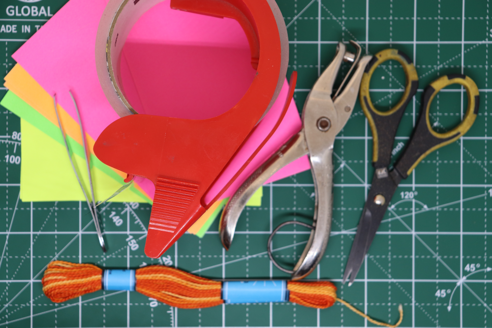 A picture of supplies: a fan of colored index cards, packing tape, a hole punch, scissors, tweezers, and embroidery thread