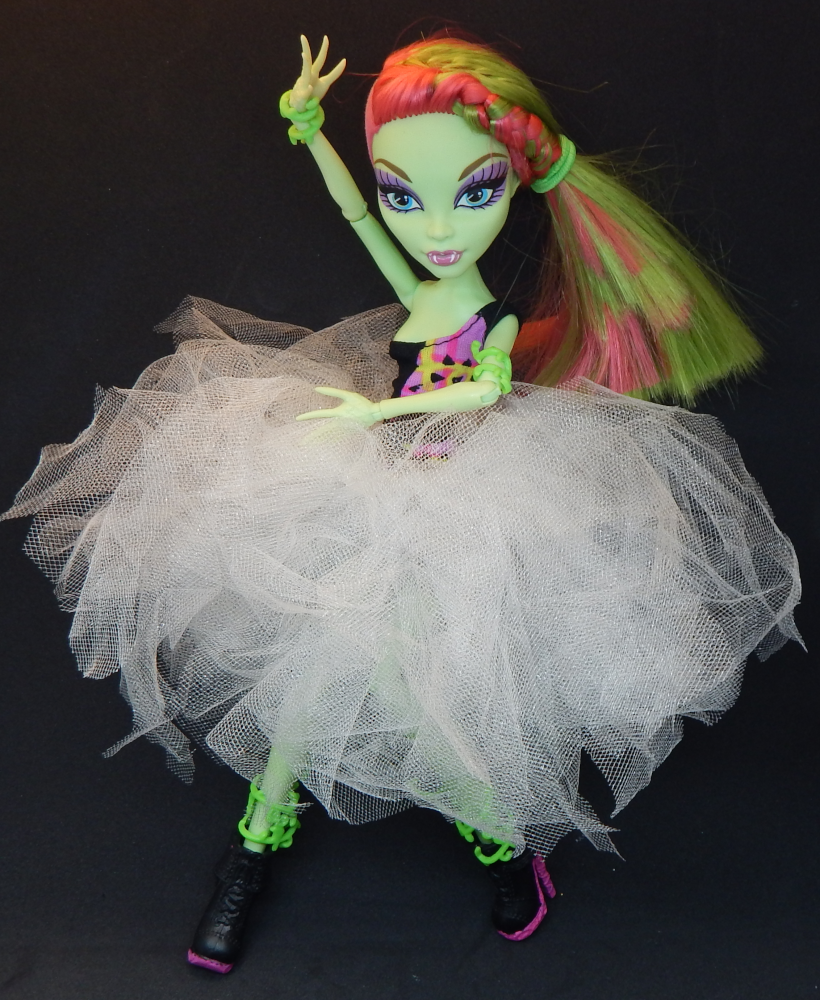 A green skinned fashion doll with pink and one curving in front of her torso. She wears a pink, green, and black one shouldered dress and a fluffy white tutu with chunky black boots with pink soles.