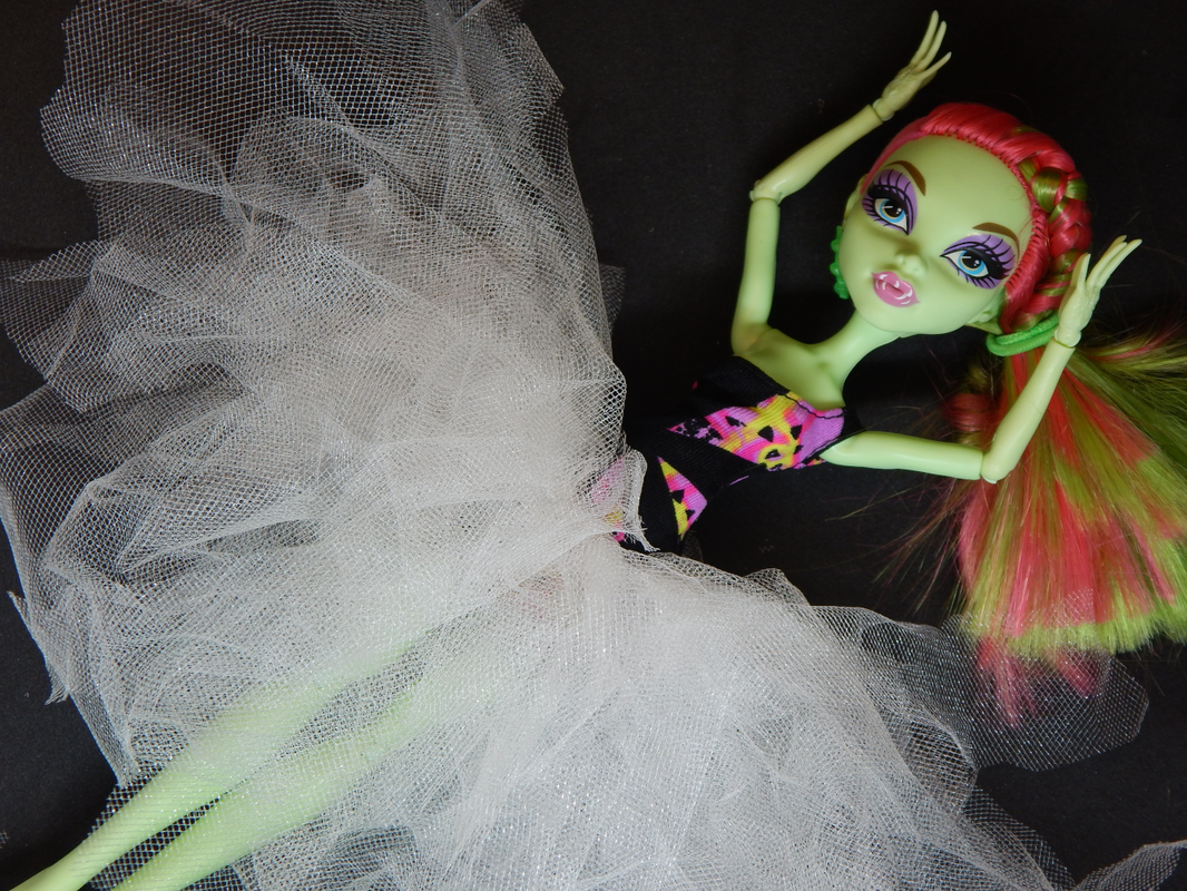 A green skinned fashion doll with pink and green hair lies on a black background with her arms reaching towards her head. She is wearing a black and pink one armed dress and a white tutu at her waist.