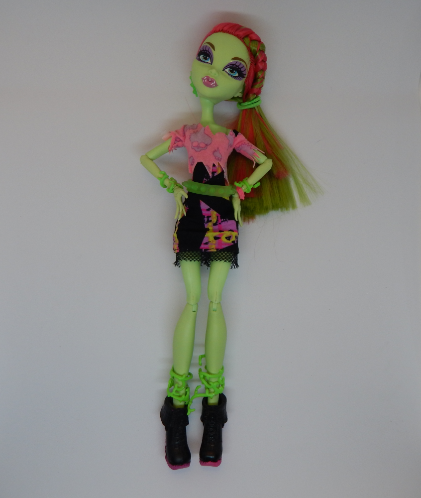 A green skinned fashion doll with pink and green hair on a white background. Her hands are on her hips and she is wearing chunky black boots.