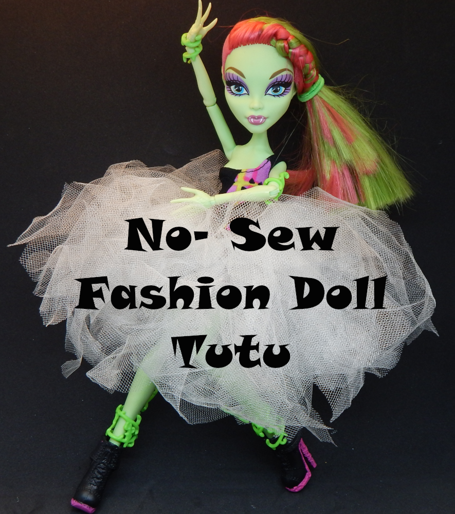 A Picture of a green skinned fashion doll with pink and green hair. she is holding her arms in a ballet like pose and wearing a tutu made of white tulle. Text across the tutu reads