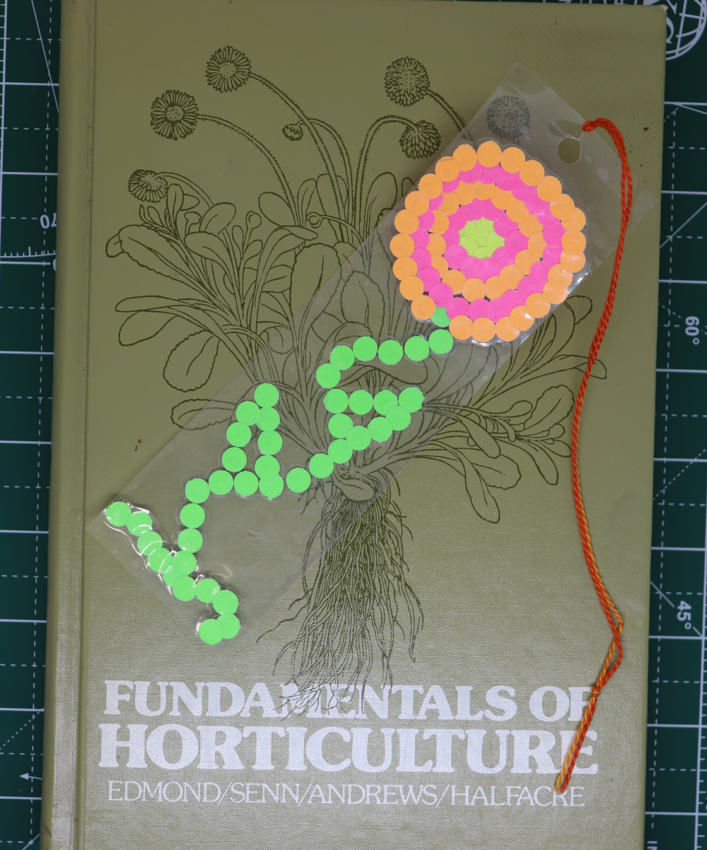 A bookmark with a flower made out of different colored paper dots rests on top of a book