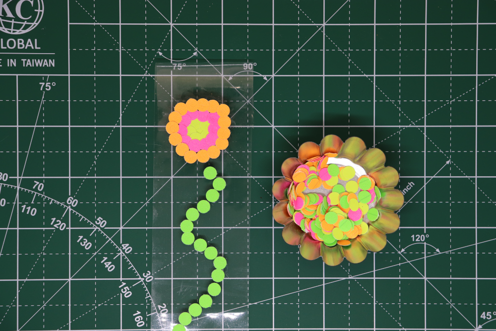 A container of colorful paper dots, by packing tape with a green paper dot stem and yellow, pink, and orange paper dots in concentric circes making the beginning of a flower