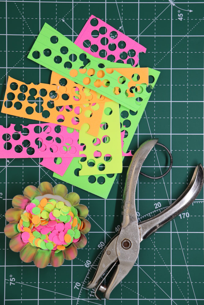 A few different pieces of paper in different colors with many punch holes in them, a small silver tin with many different colored paper dots, and a silver hole punch