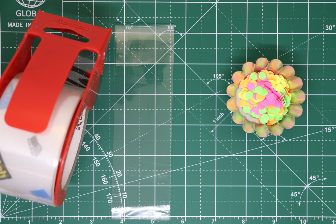 A roll of packing tape, a piece of the packing tape on the work surface, and a container of colorful paper dots