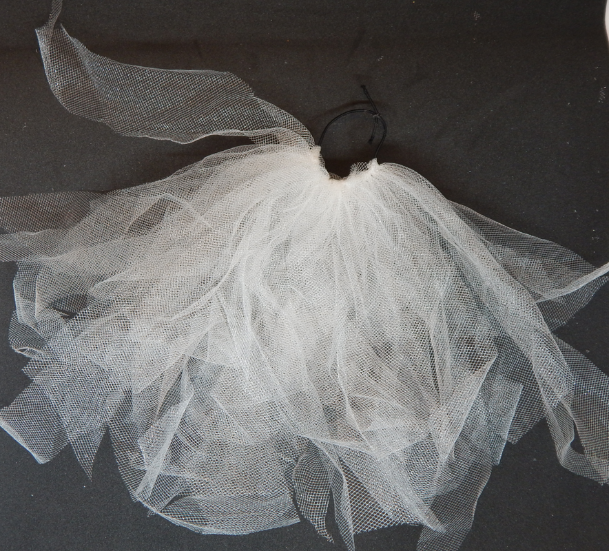Multiple pieces of white tulle attached to a black elastic band. About 1/3 the band is covered.