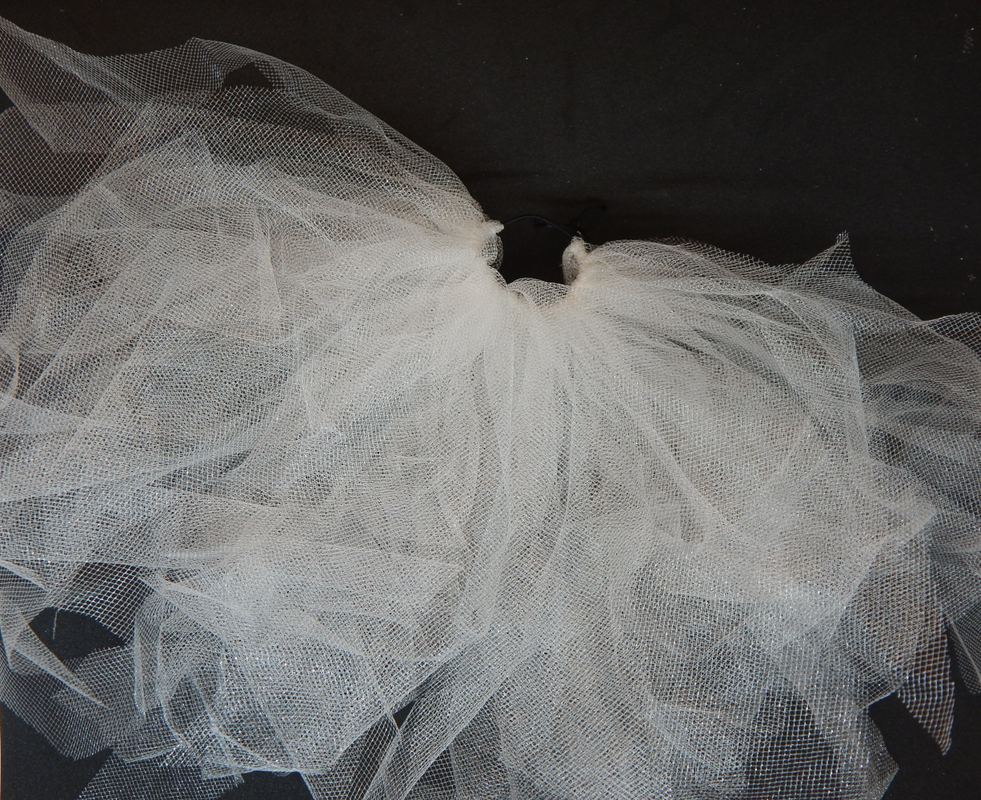 Multiple pieces of white tulle are attached to a black elastic band. IT is about halfway covered.