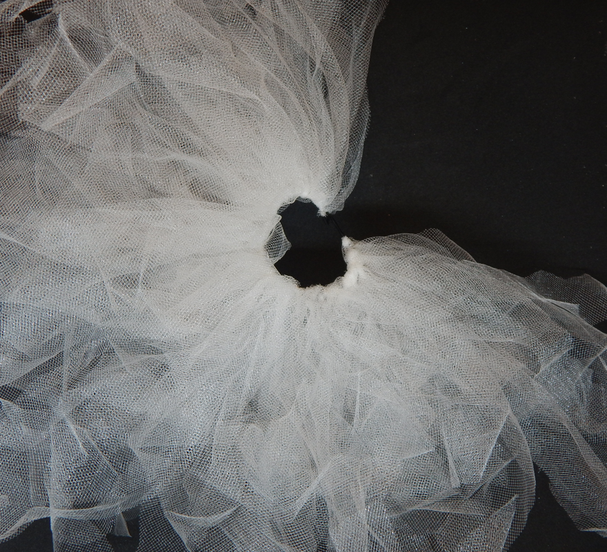 Multiple pieces of white tulle are attached to a black elastic band. The band is covered about seventy five percent.