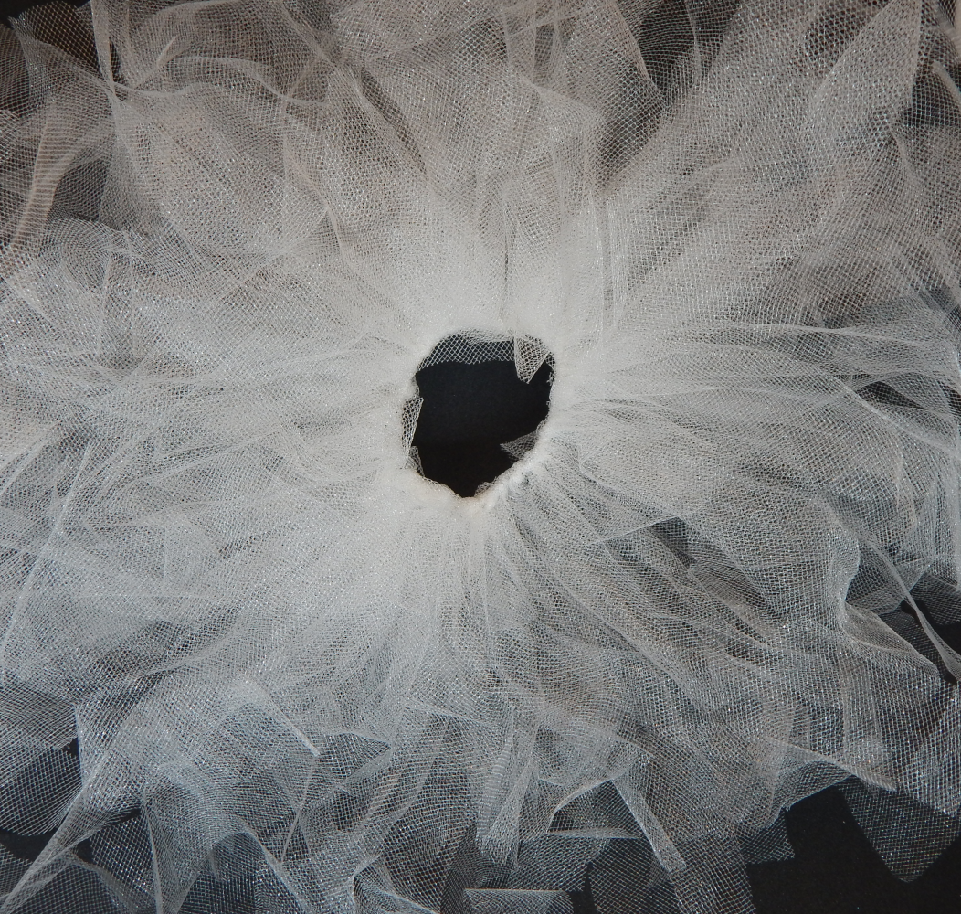 A picture of multiple tulle pieces attached to a black elastic band, covering the band completely leaving a circle of black and fanning out from it
