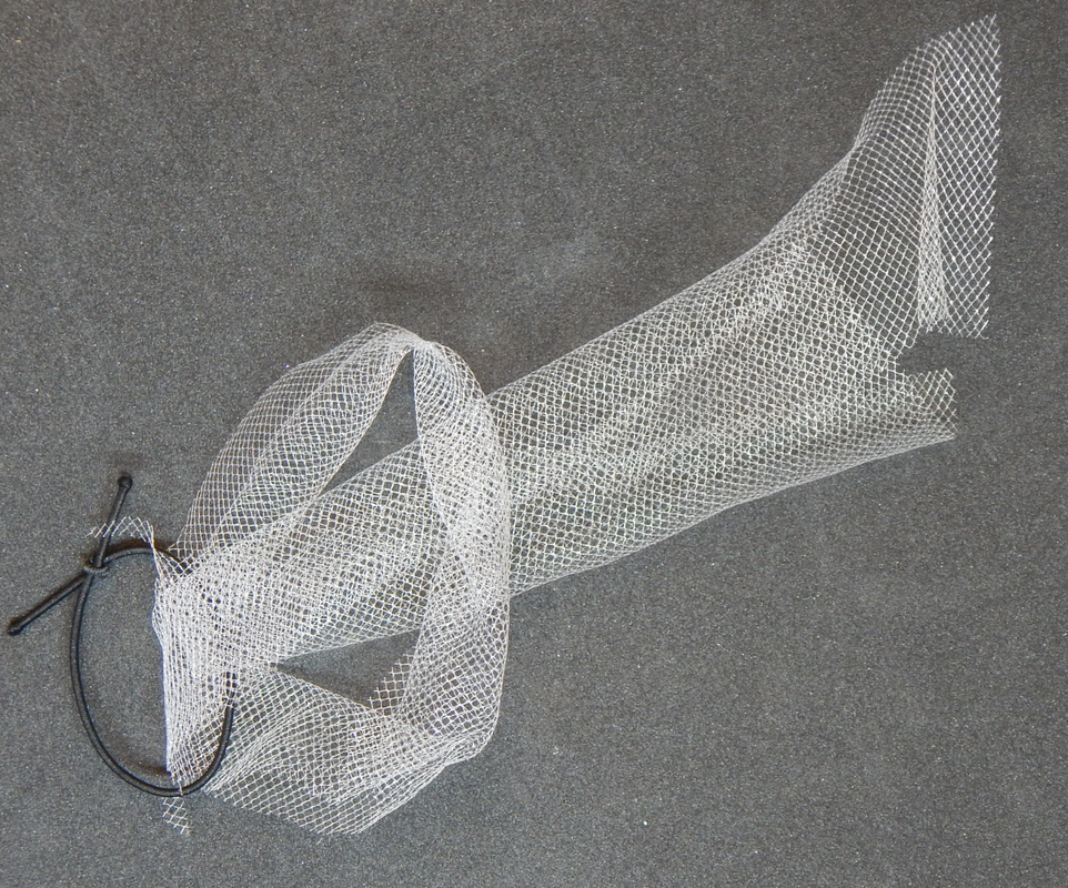 A piece of white till wrapped around a black elastic band, partway through the process of tying a lark's head knot. The two loose ends of the tulle are pulled through the loop made by folding the strip in half.