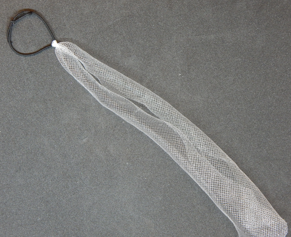 A piece of white tulle attached to a black elastic band rests diagonally on a black background
