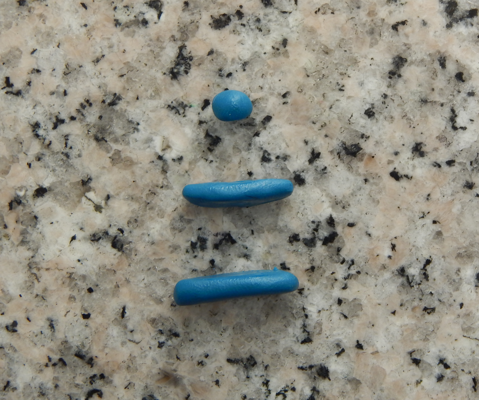 Three pieces of polymer clay: Two rounded rectangular ones and a round one