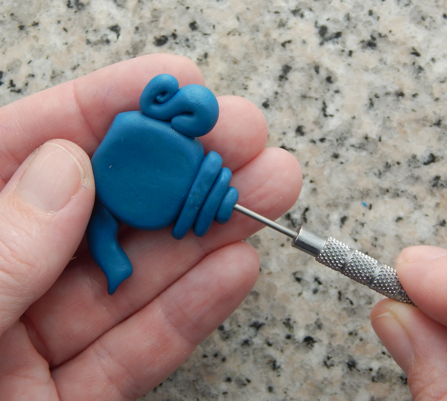One hand holds a blue teapot bead, the other inserts a needle tool through the lid