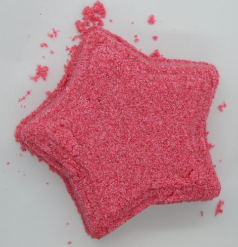 A dark pink star made up of granular sand like material, tilted slightly to the left on a white background.