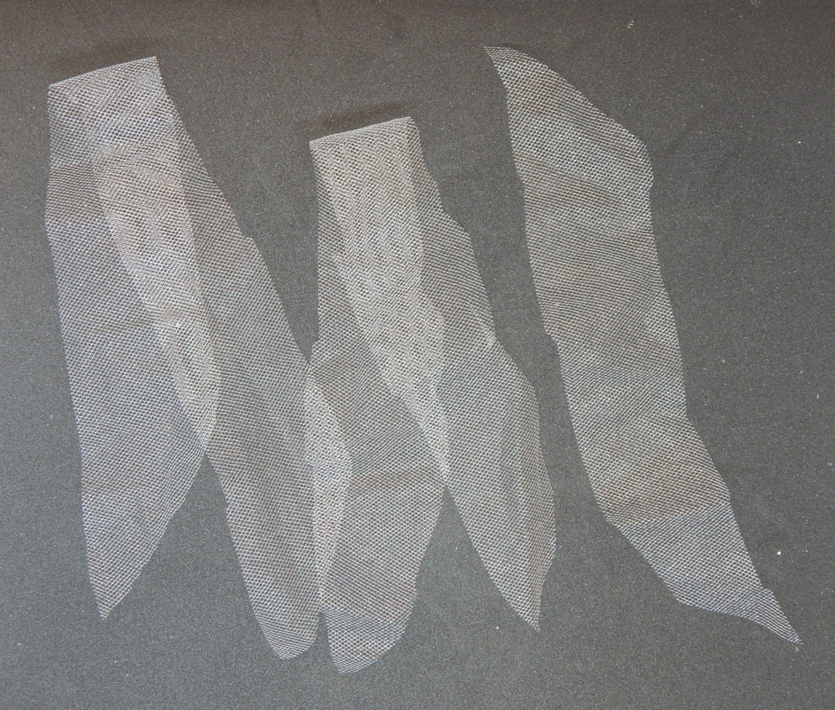 A picture of three strips of white tulle on a black background. Two of them are folded in half