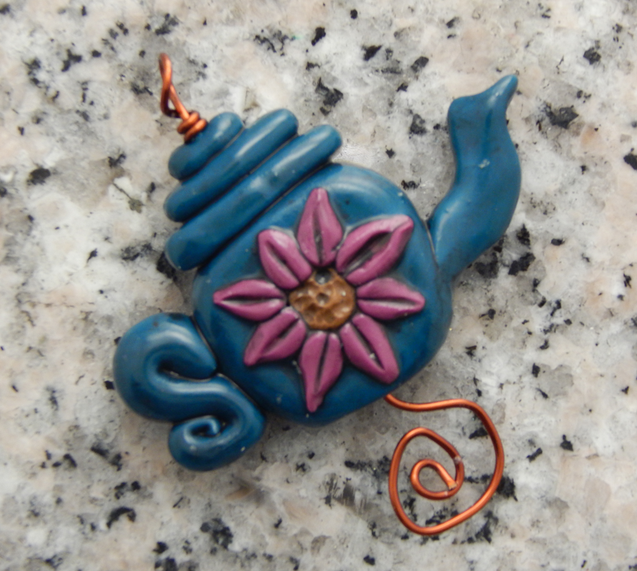 A blue teapot bad with a pink flower on a wire