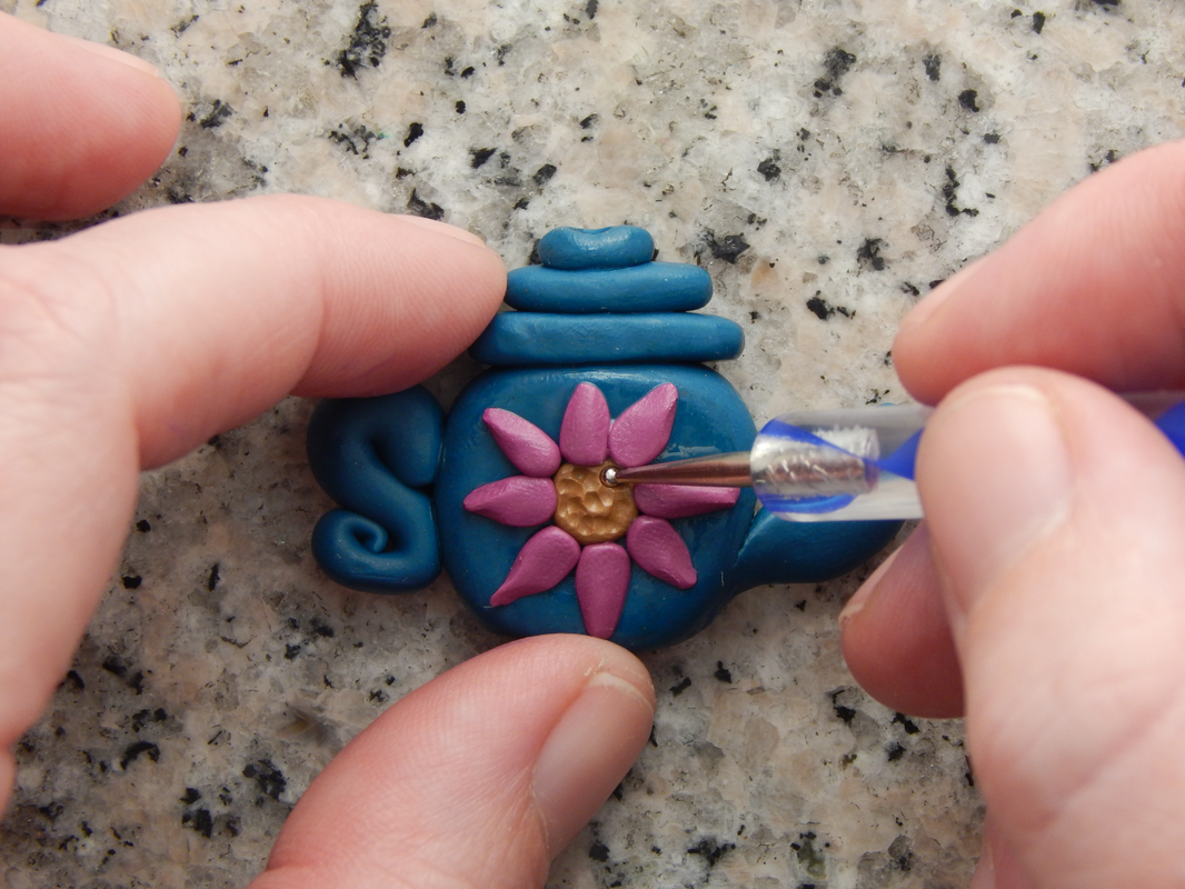 One hand holds the teapot bead while the other uses an embossing tool to press small circles into the flower center.