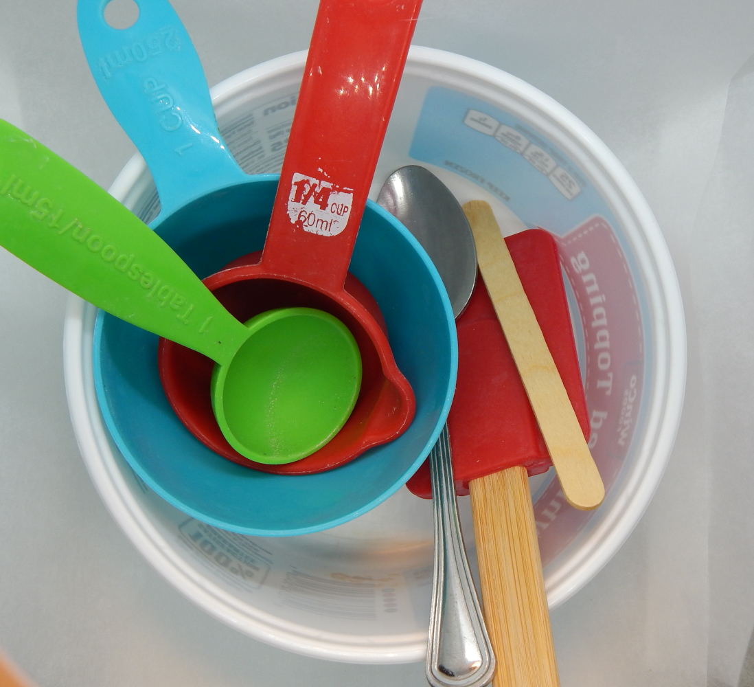 A white bowl filled with teal and red measuring cups, a green tablespoon, and a silver spoon, a popsickle stick, and a red spatula.